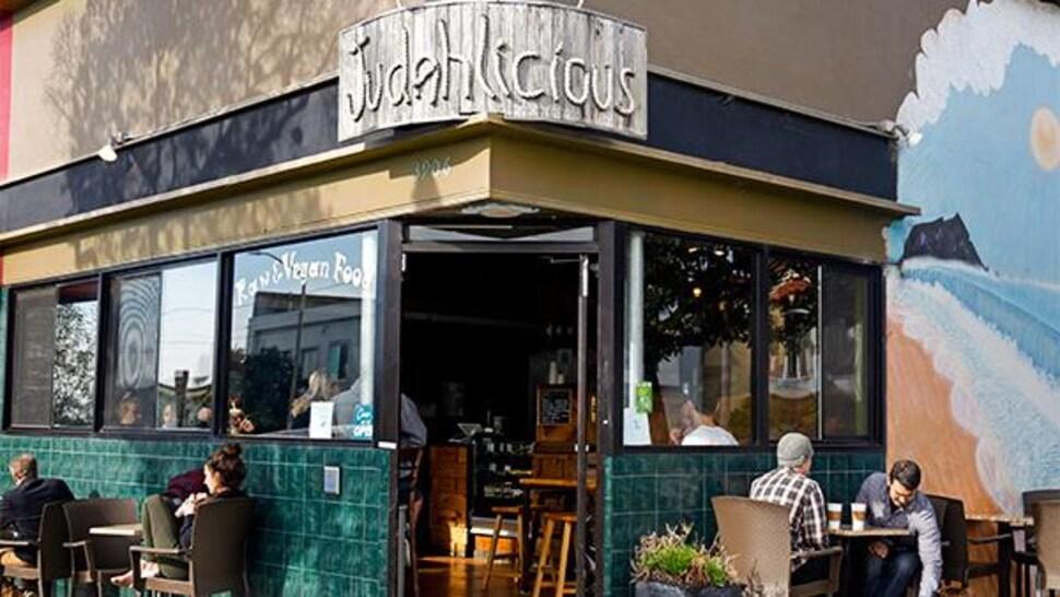 Devant l'entrée principale du restaurant, des clients sont assis à des tables à l'extérieur.