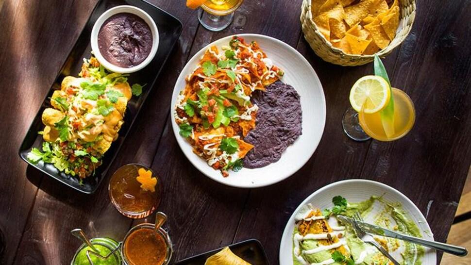 Des plats mexicains et des verres à cocktail remplis sont déposés sur une table au restaurant.