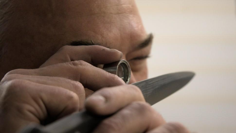 Une personne regarde un couteau de près grâce à une loupe de joaillier.