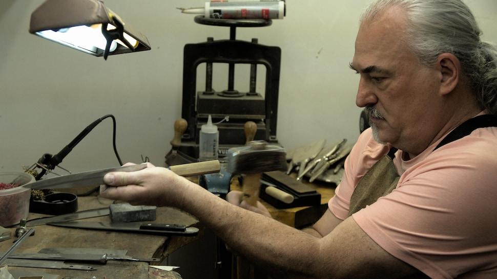 Sandro Vecchio enfonce un manche de bois sur une lame fraîchement restaurée.