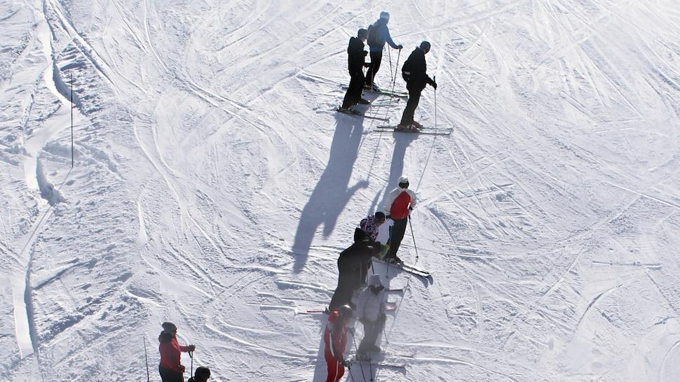 Des skieurs alpins à flanc de montagne.