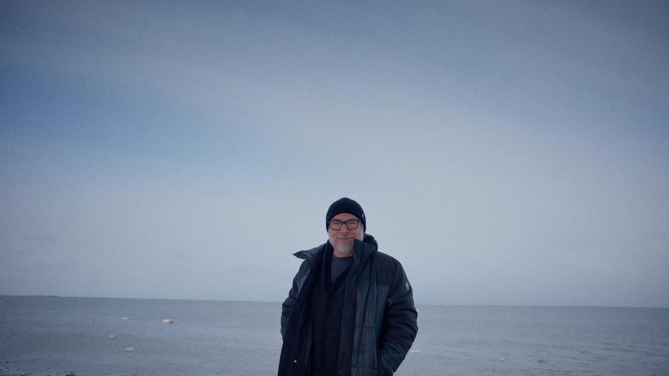 Un personne pose devant un photographe et en arrière plan, il y a l'eau du fleuve Saint-Laurent.