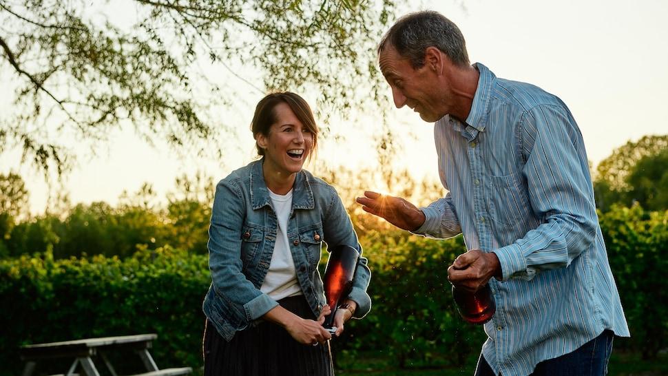 Geneviève O'Gleman rit en ouvrant une bouteille de vin avec les conseils du propriétaire à ses côtés.