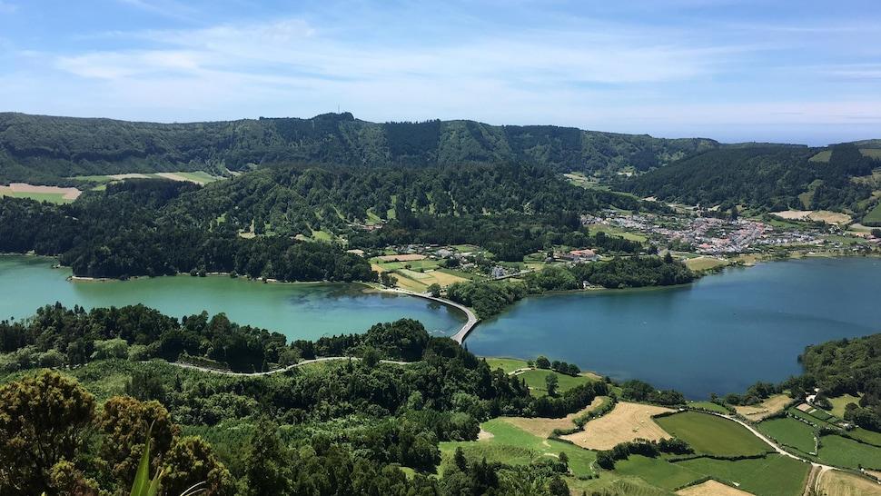 Un paysage montagneux et verdoyant séparé par un cours d'eau.