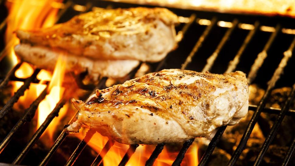 Deux poitrines de poulets qui grillent sur le BBQ avec des flammes.