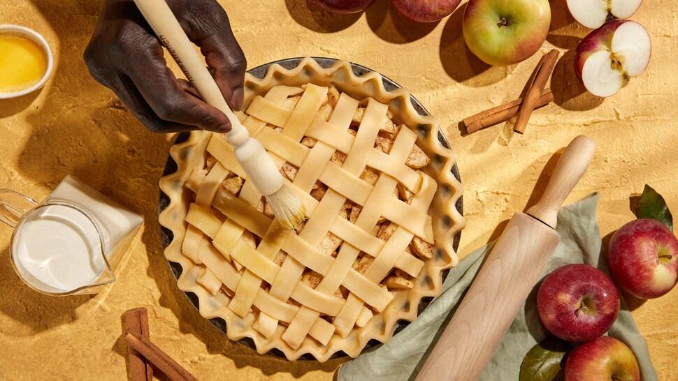 Une tarte aux pommes avec des pommes autour.