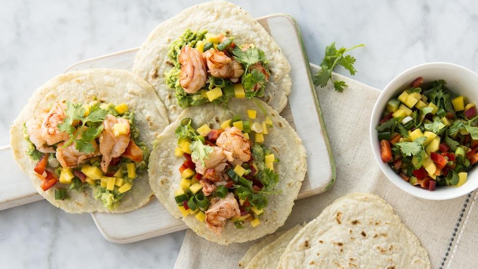Une planche de bois sur laquelle il y a trois tacos aux crevettes, à la salsa et à la mangue.