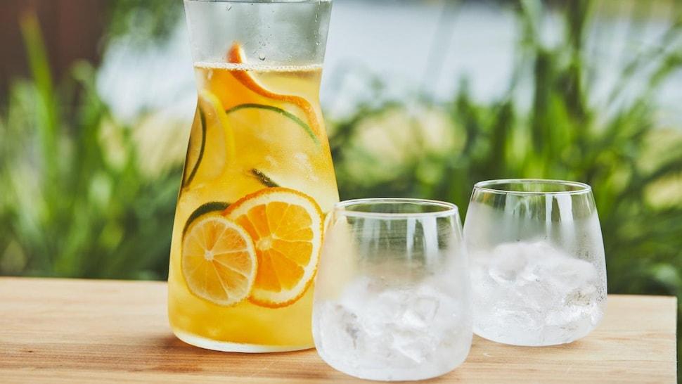 Un pichet avec de l'agua fresca aux agrumes et deux verres avec des glaçons.