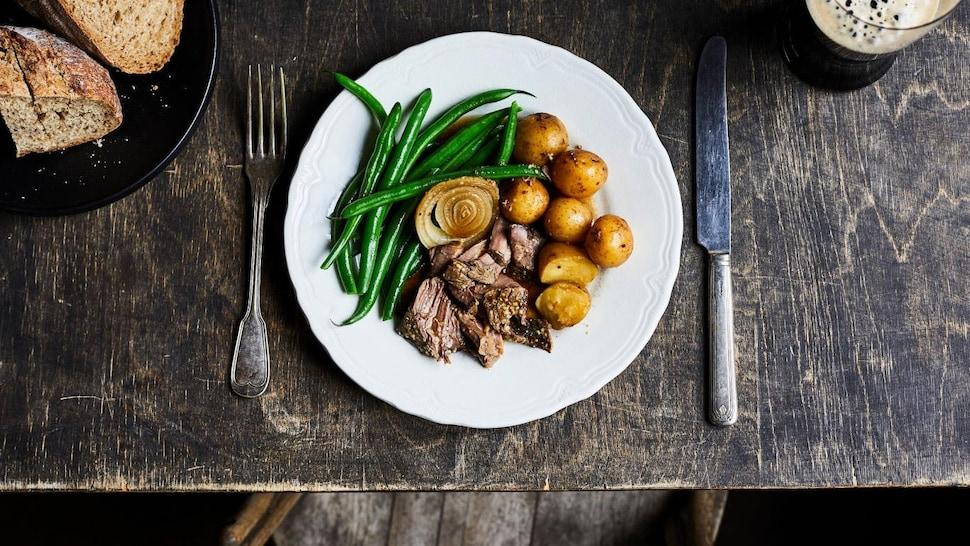 Une assiette avec des morceaux de bœuf, accompagnés de pommes de terre, d'un oignon et d'haricots verts.
