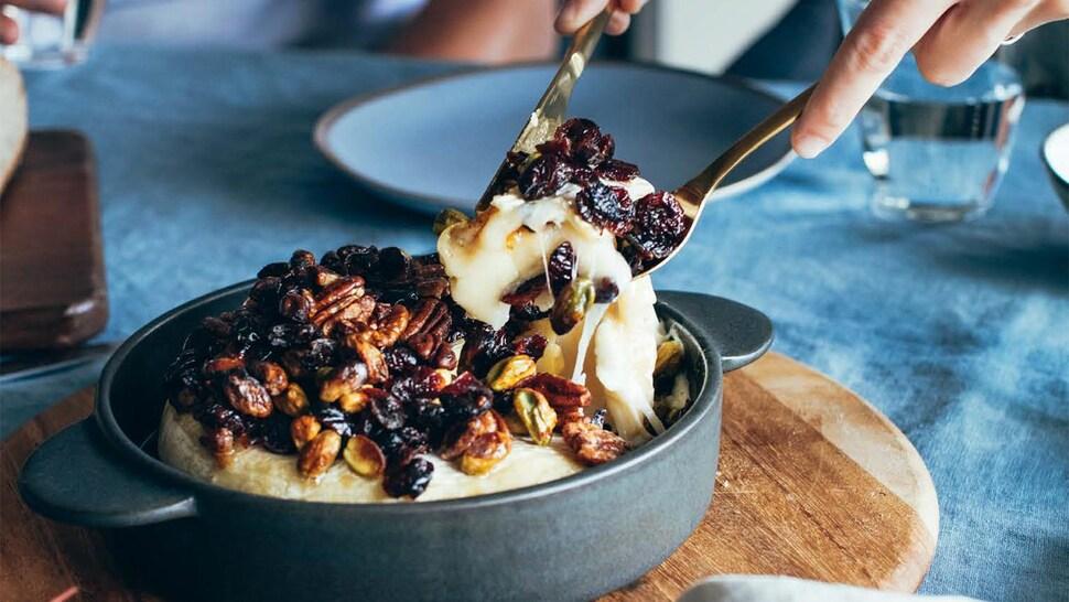 Une personne sert une portion de brie fondant aux pistaches, pacanes et canneberges.