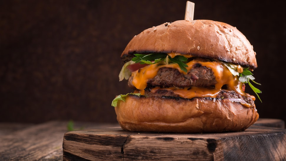Un burger garni d'herbes fraîches et d'une sauce orangée.
