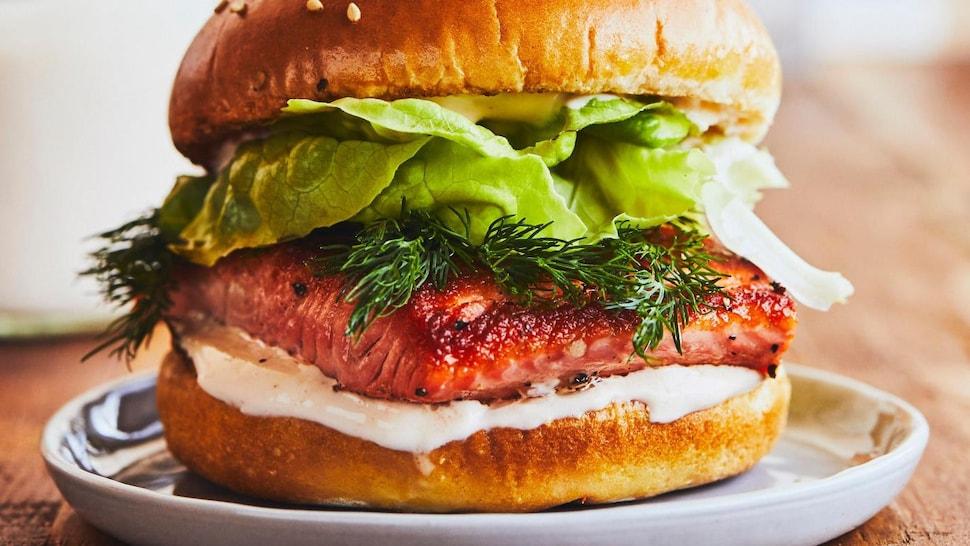 Un burger garni d'un morceau de truite, de laitue, d'aneth et de mayonnaise dans une assiette.