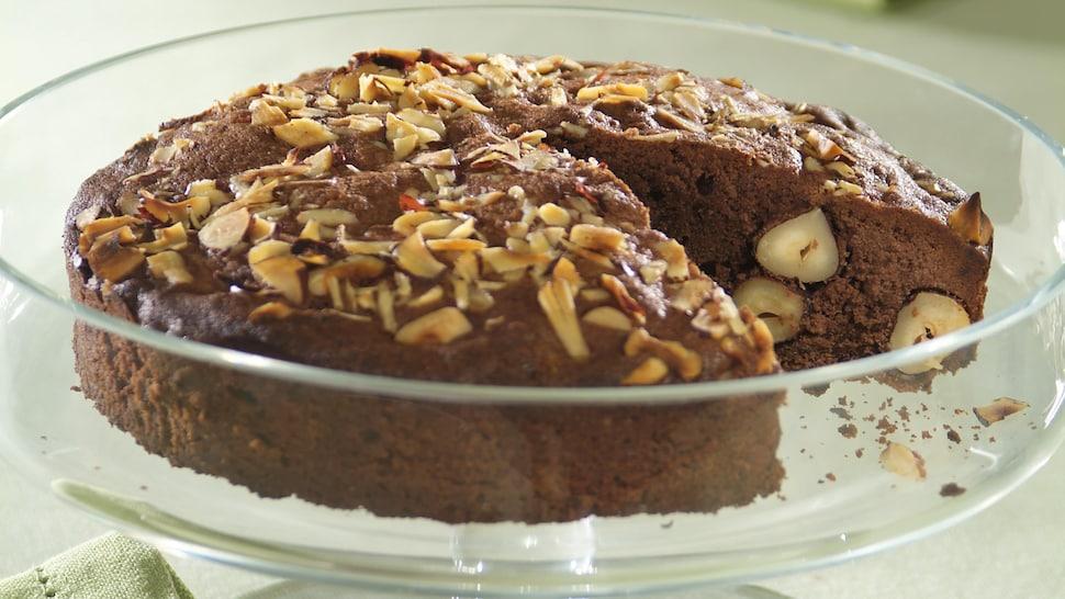 Un gâteau au chocolat garni de noix sur un présentoir à gâteau en vitre.