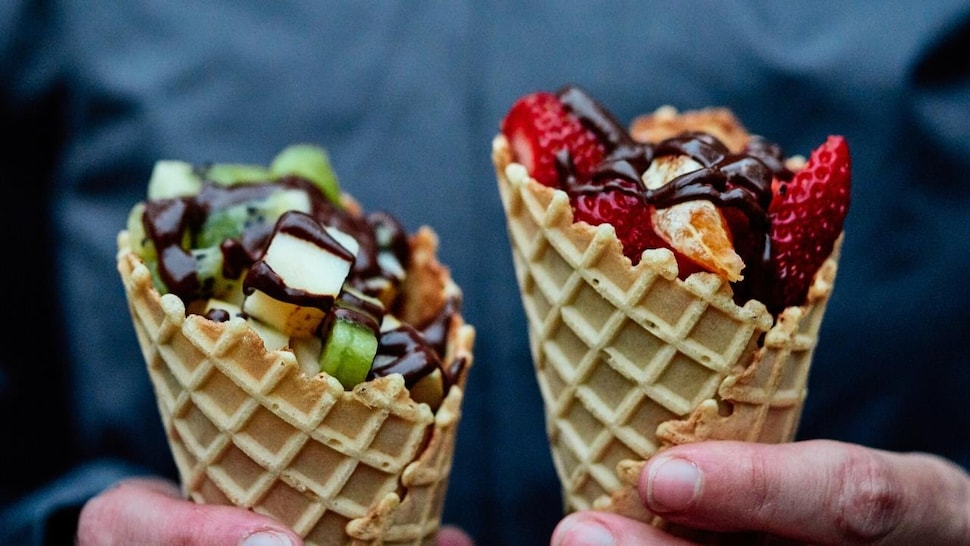 Deux cônes avec des fruits et de la fondue au chocolat.
