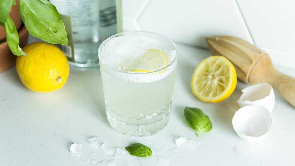 Une personne verse un gin citron-basilic sour dans un verre.