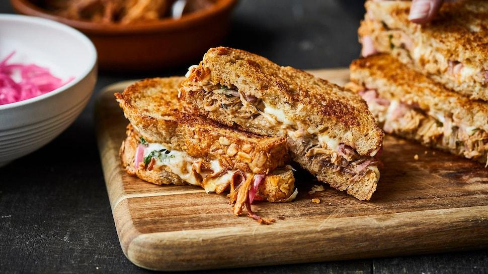 Deux grilled cheese au porc effiloché sur une planche de bois.