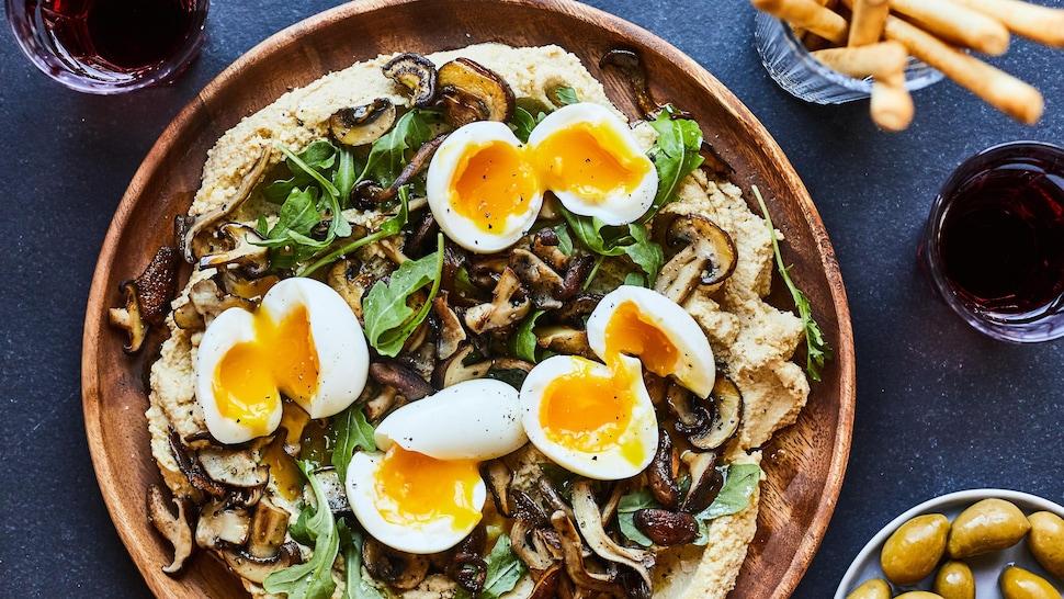 Houmous aux champignons dans une assiette en bois avec des oeufs mollets sur le dessus.