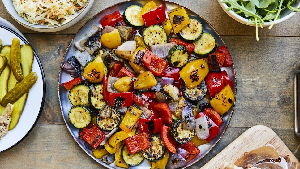 Une grande assiette noire avec des légumes grillés.