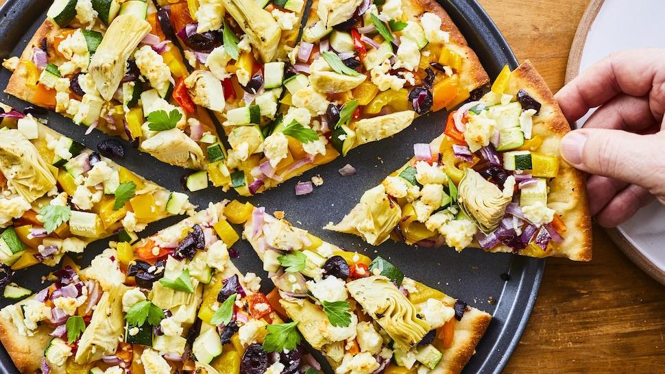 Une pizza garnie de coeurs d'artichauts, d'olives, de poivrons et d'oignons rouges sur une plaque cuisson avec une main qui prend une pointe.