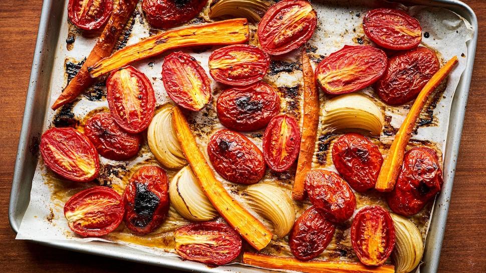 Plaque recouverte de tomates rôties, carottes et oignons.