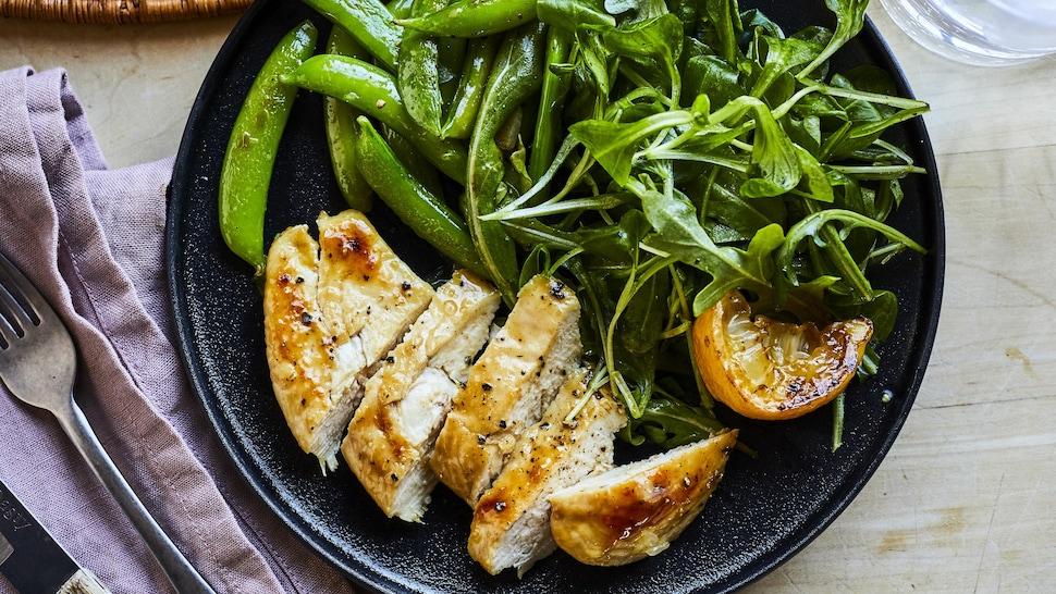 Assiette de poulet au miel et au citron avec tomates et roquette.