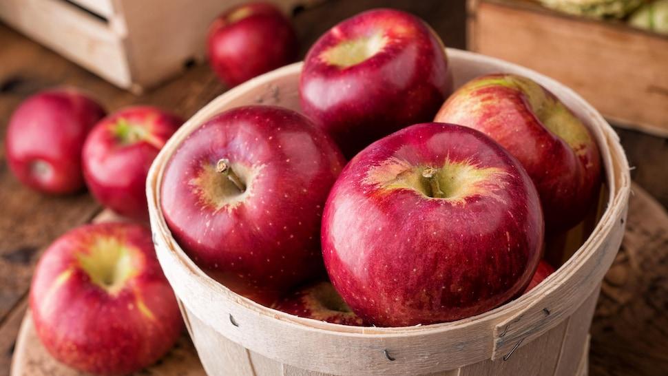Un panier en bois rempli de pommes.