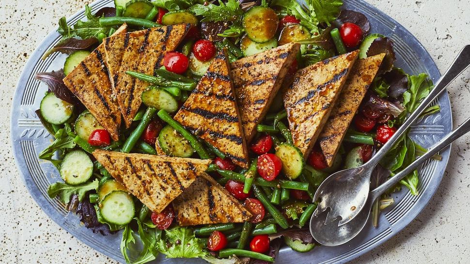 Grand plat de salade d'été avec tofu grillé, concombres, tomates et fèves vertes.