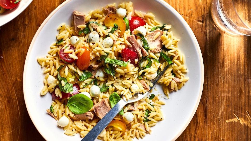 Salade d'orzo aux tomates et au bocconcini dans une assiette.