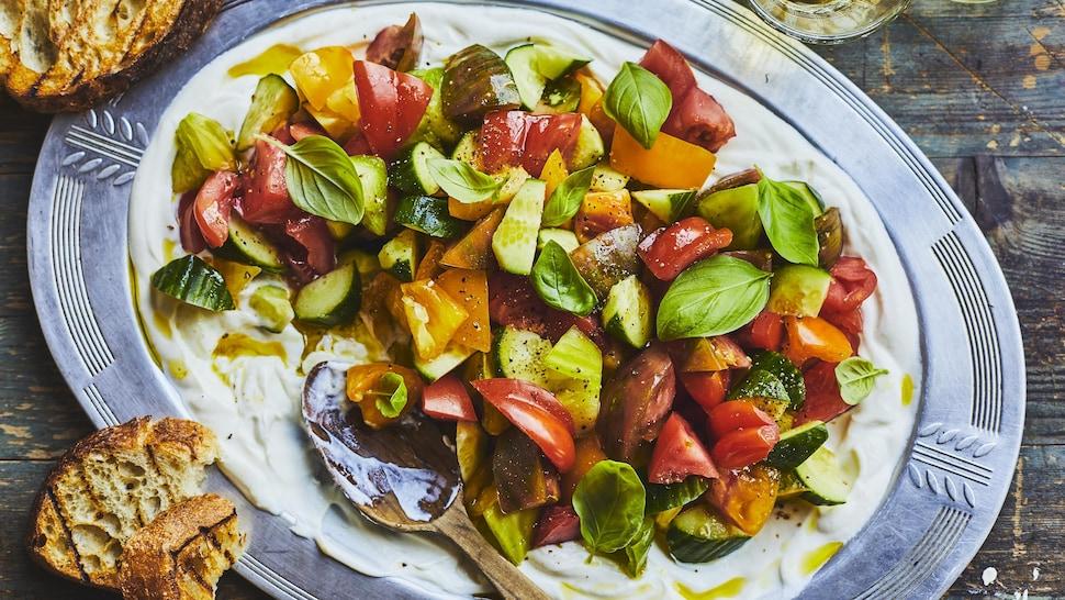 Salade de tomates à la ricotta fouettée dans une assiette.