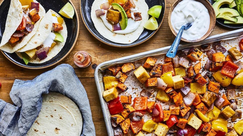 Tacos végé à la plaque dans deux assiettes et légumes sur une plaque.