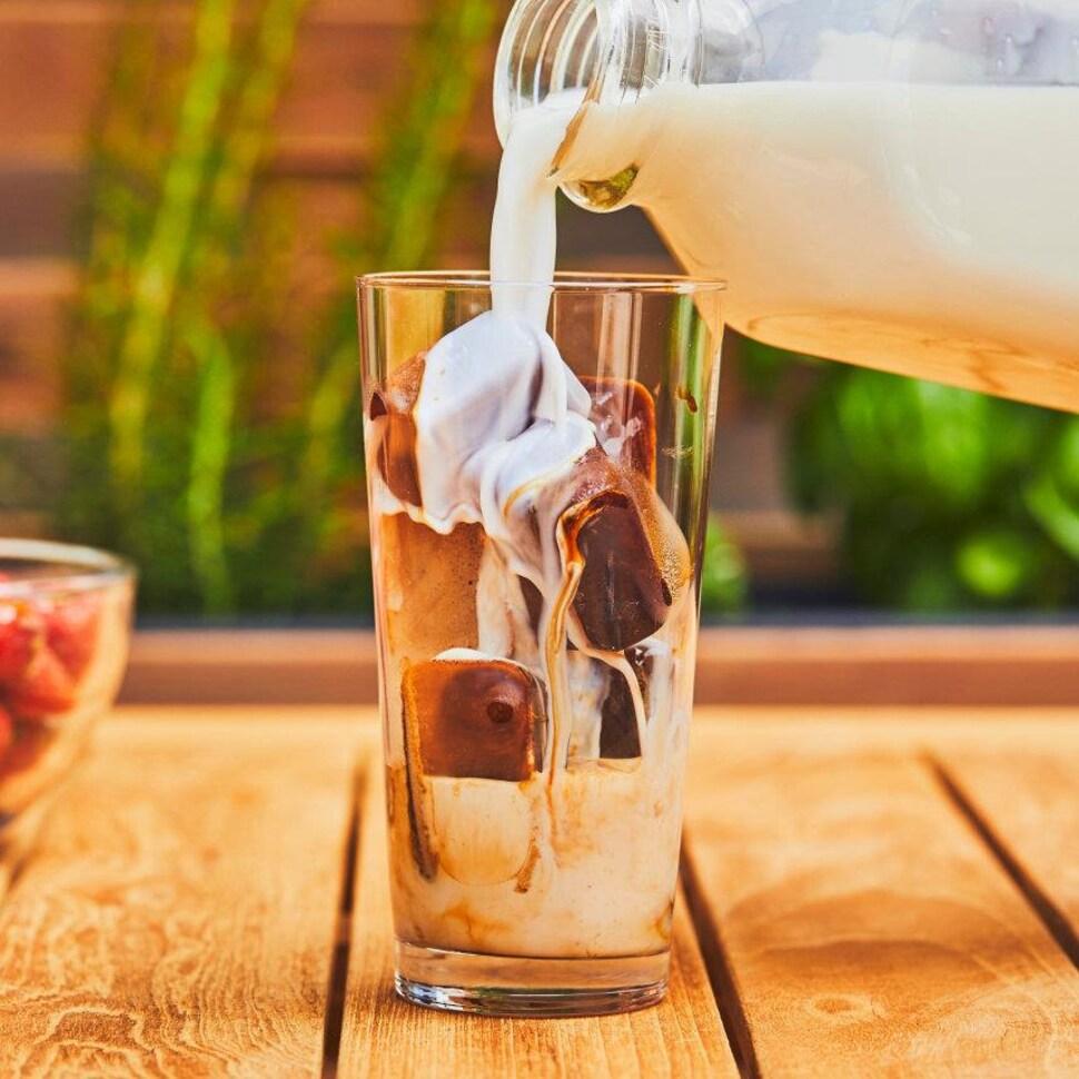Une main verse du lait dans un grand verre de glaçons et de café.