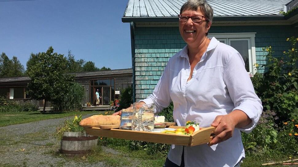 La fromagère sert un plateau de fromages aux visiteurs.