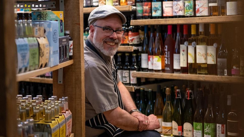 François J. Lebel devant des bouteilles de cidres.