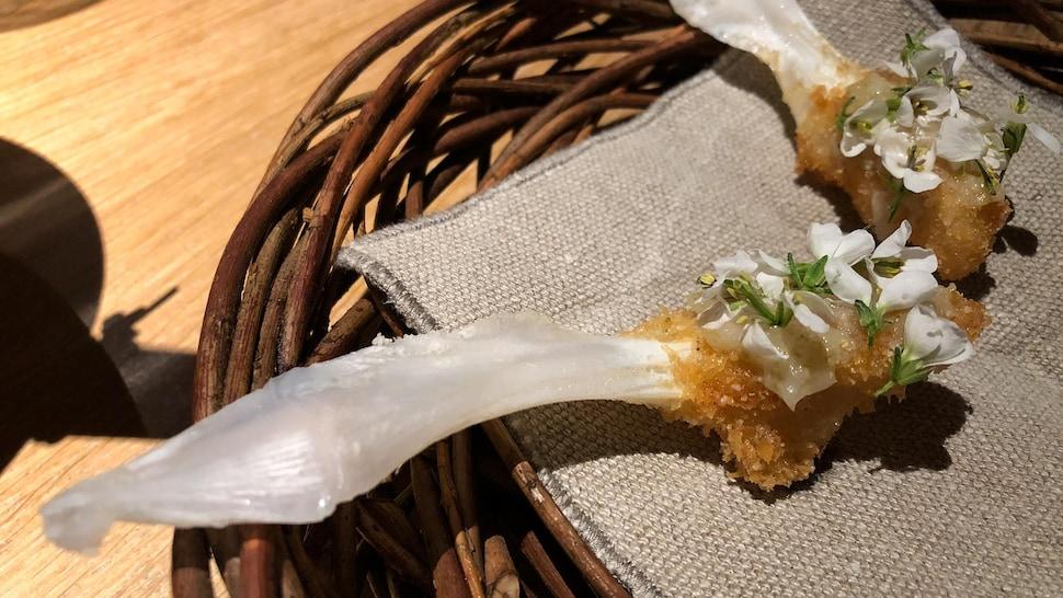 Un schnitzel de langue de morue décoré de fleurs de wasabi. À déguster tel un suçon.