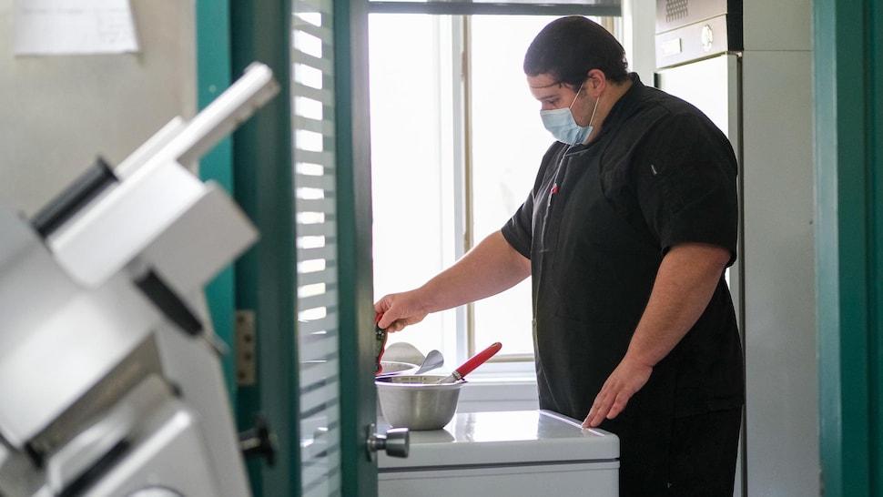 Un chef surveille la température au-dessus d'une marmite.