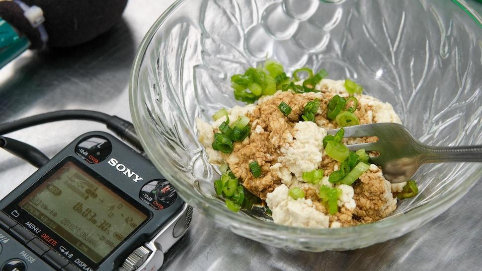 Du tofu fraîchement préparé dans un bol transparent déposé aux côtés d'un enregistreur numérique.