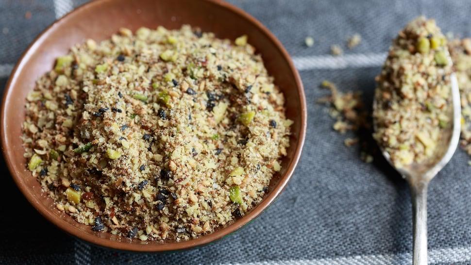 Du dukkah, un mélange d'épices et de noix concassées, dans un bol sur une table.
