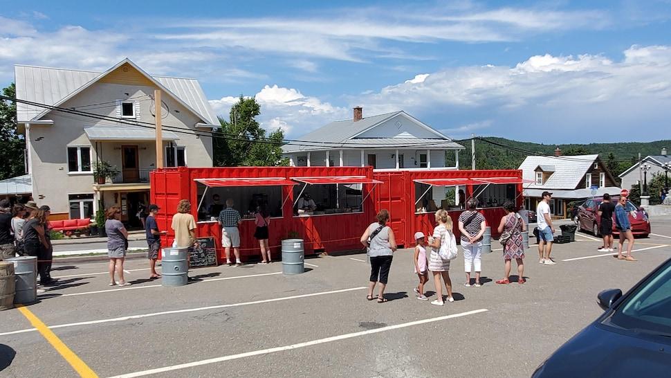 Un conteneur transformé en cantine accueille des dizaines de clients, qui font la file en maintenant une certaine distanciation physique.