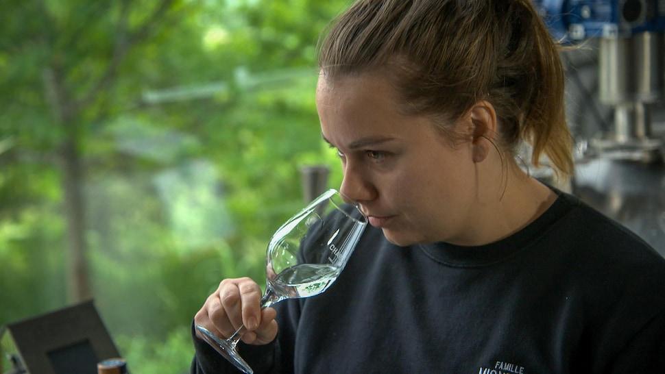 Une femme sent les parfums d'une eau-de-vie dans un verre.