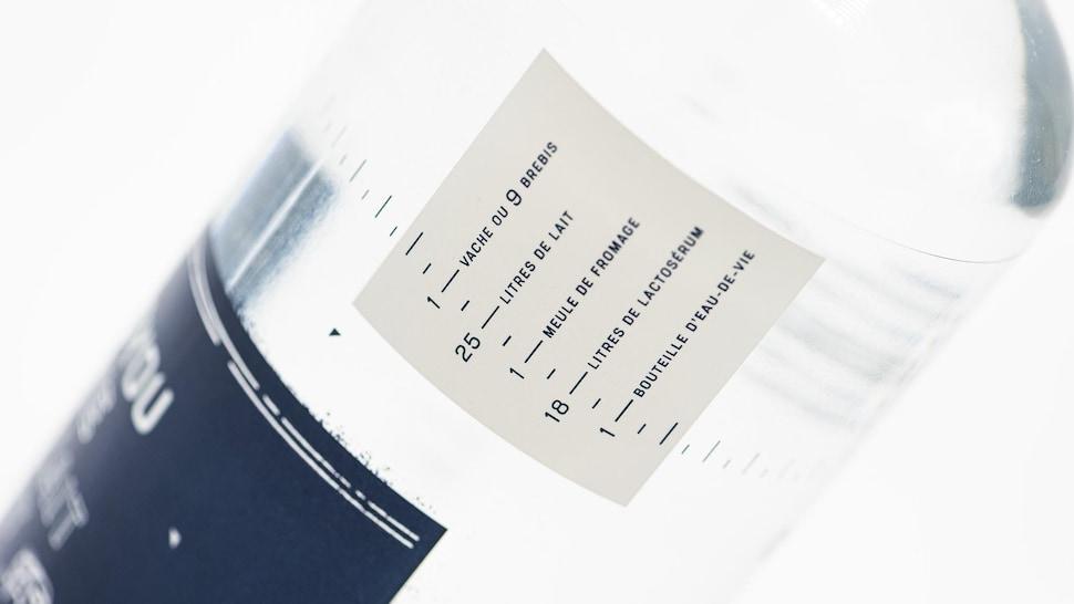 Une bouteille d'eau-de-vie avec une étiquette indiquant entre autre la quantité de litres de lait nécessaires à sa fabrication.