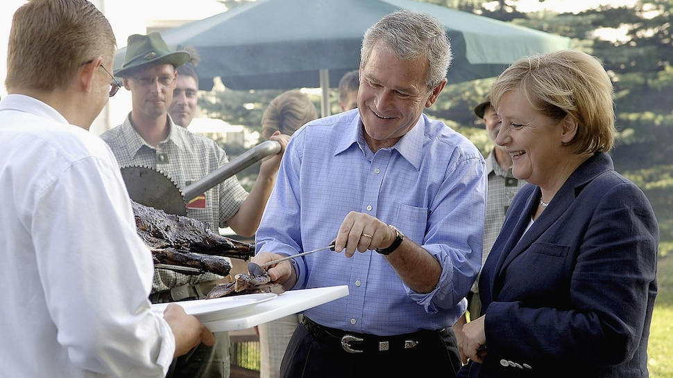 L'ancien président des États-Unis, George W. Bush, coupe un morceaux de viande grillée pour la chancelière allemande, Angela Merkel, lors d'un barbecue dans le village de Trinwillershagen, en Allemagne.