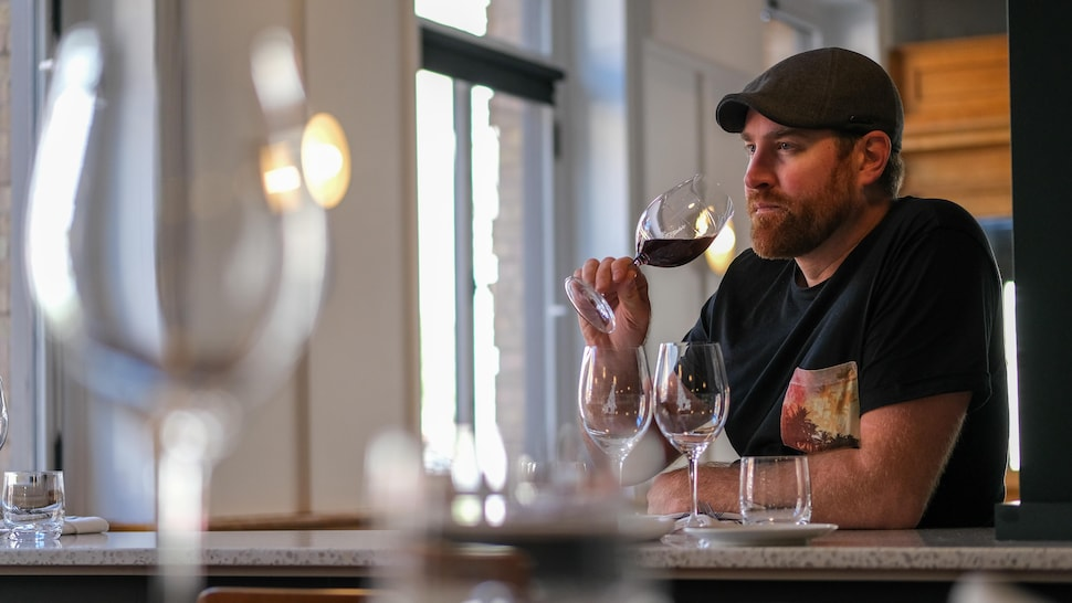 Un homme hume un verre de vin rouge.