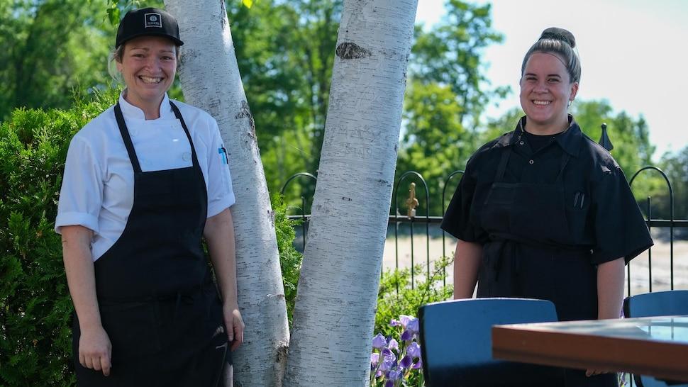 Deux femmes en habit de cuisinière regarde la caméra.