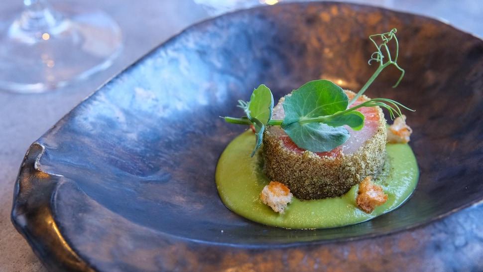 Un gravlax de truite et de bar rayé en croûte de menthe poivrée, déposé sur un coulis de pois verts accentué de croûtons de pain au maïs au paprika fumé.
