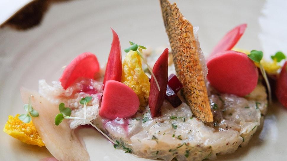 Un tartare de doré avec des légumes colorés et une chip de peau de saumon.