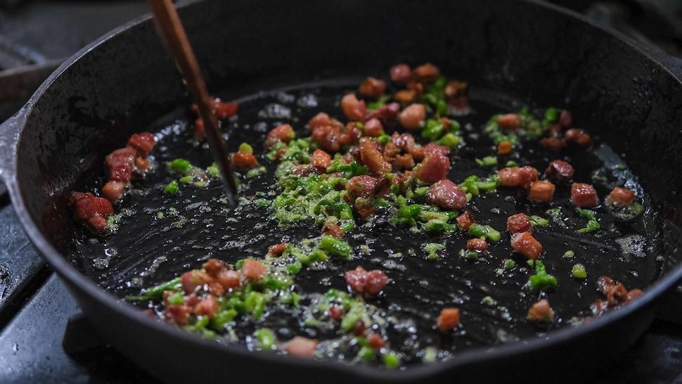 De la fleur d'ail et des lardons de bacon dans un poêlon en fonte.