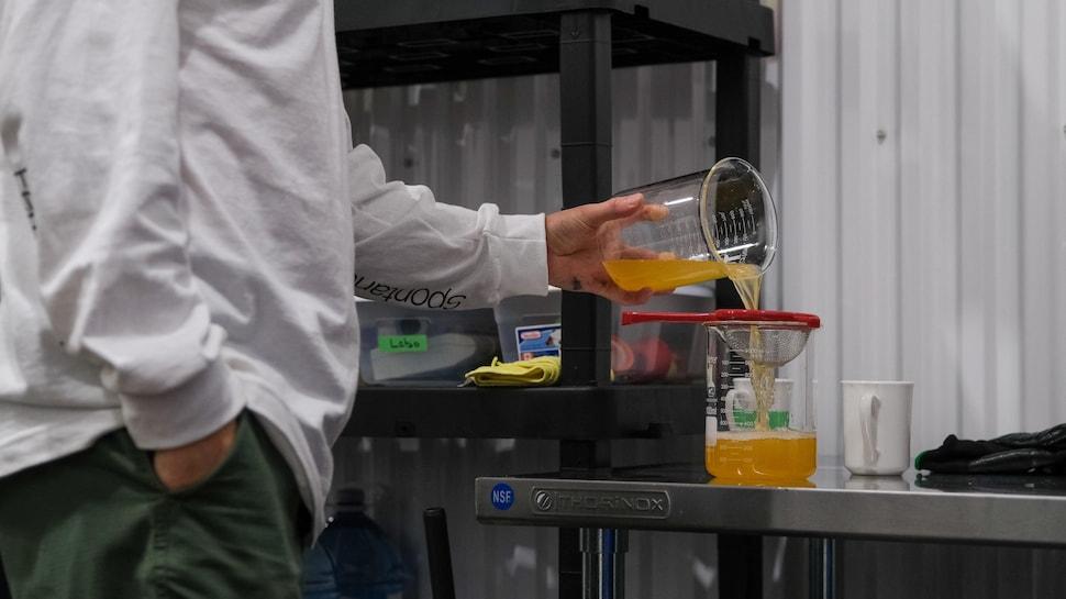Une personne verse du jus dans une passoire.
