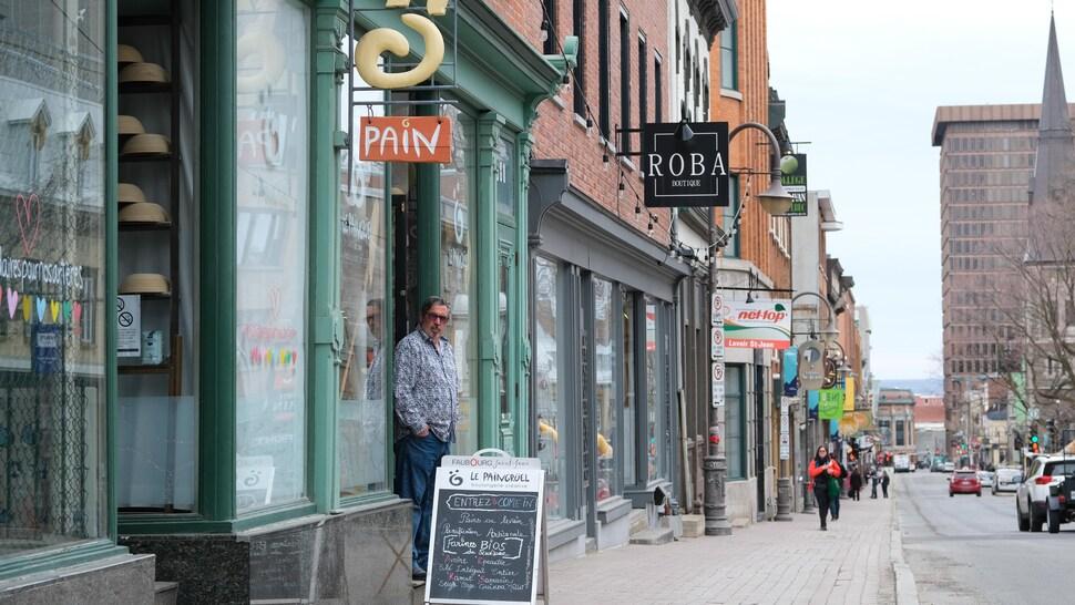Un boulanger devant son commerce.