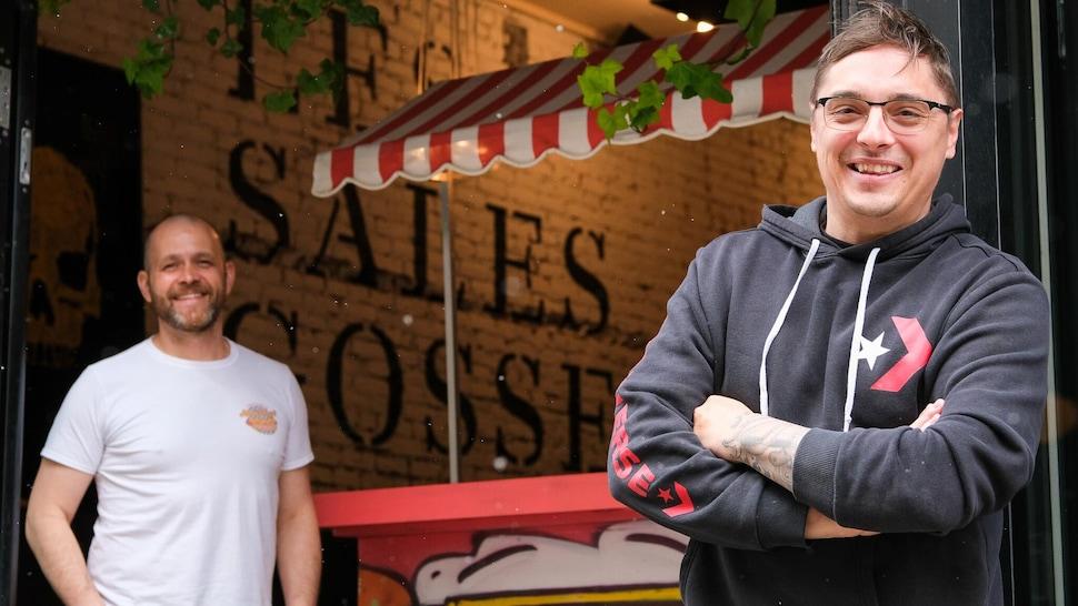 Deux hommes d'affaires devant leur restaurant.
