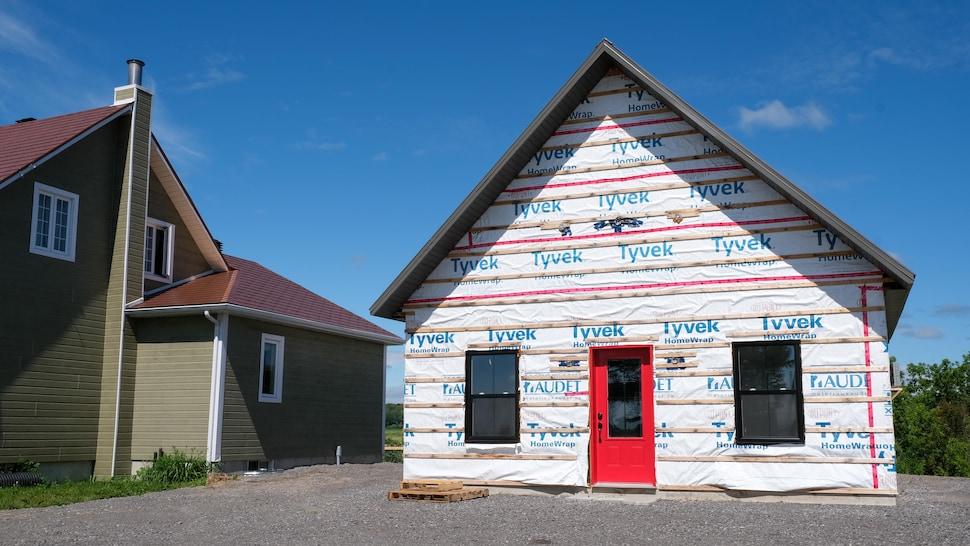 Un bâtiment en construction avec une porte rouge.
